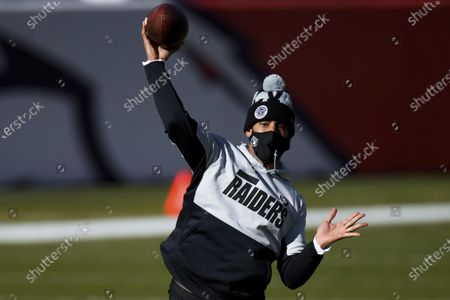 Las Vegas Raiders quarterback Marcus Mariota (8) warms up by throwing a pass against the Denver Broncos before an NFL football game, in Denver