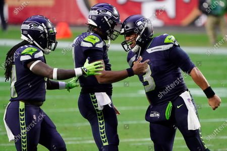 Seattle Seahawks quarterback Russell Wilson (3) celebrates after a touchdown against the San Francisco 49ers with quarterback Geno Smith and linebacker Ray-Ray Armstrong, left, during the second half of an NFL football game, in Glendale, Ariz
