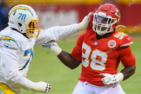 Kansas City Chiefs defensive tackle Tershawn Wharton (98) and Los Angeles Chargers guard Trai Turner (70) during the first half of an NFL football game, in Kansas City, Mo