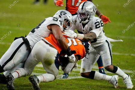 Las Vegas Raiders middle linebacker Raekwon McMillan (54) and cornerback Nevin Lawson (26) tackle Denver Broncos running back Melvin Gordon (25) during the first half of an NFL football game, in Denver