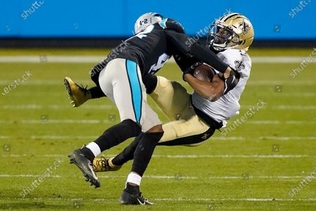 New Orleans Saints wide receiver Emmanuel Sanders is tackled by Carolina Panthers safety Sam Franklin during the second half of an NFL football game, in Charlotte, N.C