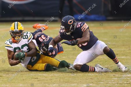 Green Bay Packers wide receiver Marquez Valdes-Scantling (83) is tackled by Chicago Bears free safety Eddie Jackson (39) and inside linebacker Roquan Smith (58) during the first half of an NFL football game, in Chicago