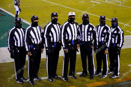 Stock Image of Officials Patrick Holt (106), Greg Yette (38), Boris Cheek (41), Roy Ellison (81), Greg Bradley (98) and James Coleman (95) pose for a group portrait before an NFL football game between the Philadelphia Eagles and the Washington Football Team, in Philadelphia