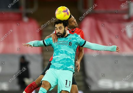 Liverpool's Mohamed Salah and Southampton's Ryan Bertrand, right, compete to head the ball during the English Premier League soccer match between Southampton and Liverpool at St Mary's Stadium, Southampton, England
