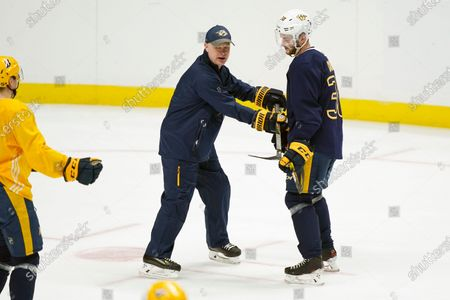 Nashville Predators head coach John Hynes demonstrates a play with defenseman Jeremy Davies (38) during NHL hockey training camp, in Nashville, Tenn