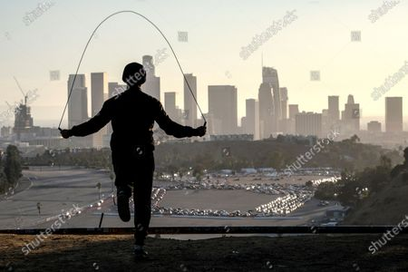 Alex Gonzalez, 19, jumps rope on Angel's Point at Elysian Park as motorists wait in long lines to take a coronavirus test in a parking lot at Dodger Stadium, in Los Angeles