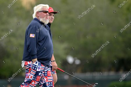John Daly and his son Little John Daly walk off the 18th green after finishing during the final round of the PNC Championship golf tournament, in Orlando, Fla