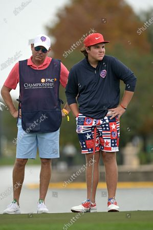 Stock Photo of Little John Daly, son of golfer John Daly, waits to putt on the 18th green during the final round of the PNC Championship golf tournament, in Orlando, Fla