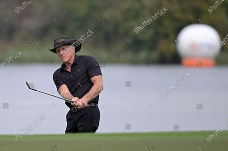 Greg Norman, of Australia, watches after hitting from a bunker onto the 18th green during the final round of the PNC Championship golf tournament, in Orlando, Fla