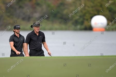 Stock Image of Greg Norman, right, of Australia, and his son Greg Norman Jr. walk on the 18th fairway during the final round of the PNC Championship golf tournament, in Orlando, Fla