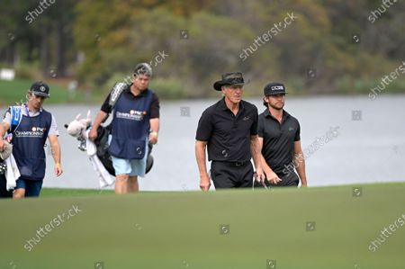 Stock Picture of Greg Norman, of Australia, and his son Greg Norman Jr., right, walk on the 18th fairway during the final round of the PNC Championship golf tournament, in Orlando, Fla