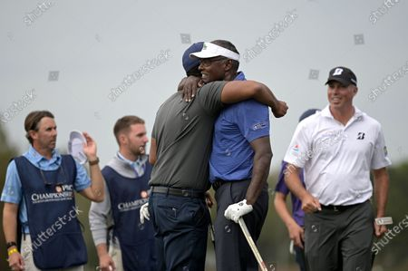 Vijay Singh, second from right, of Fiji Islands, hugs his son Qass after finishing on the 18th green during the final round of the PNC Championship golf tournament, in Orlando, Fla