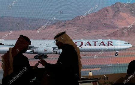 Stock Picture of Journalists chat as video of a plane carrying Qatari Emir Sheikh Tamim bin Hamad Al Thani is shown on a screen while landing at at Al Ula airport, where the 41st Gulf Cooperation Council (GCC) meeting takes place, in Saudi Arabia, . Al Thani's arrival in the kingdom's ancient desert city of Al-Ula on Tuesday was broadcast live on Saudi TV. He was seen descending from his plane and being greeted with a hug by the Saudi crown prince. The diplomatic breakthrough comes after a final push by the outgoing Trump administration and fellow Gulf state Kuwait to mediate an end to the crisis
