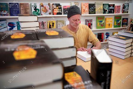Swedish writer John Ajvide Lindqvist photographed signing books in Stockholm, Sweden