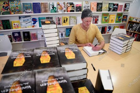 Stock Picture of Swedish writer John Ajvide Lindqvist photographed signing books in Stockholm, Sweden