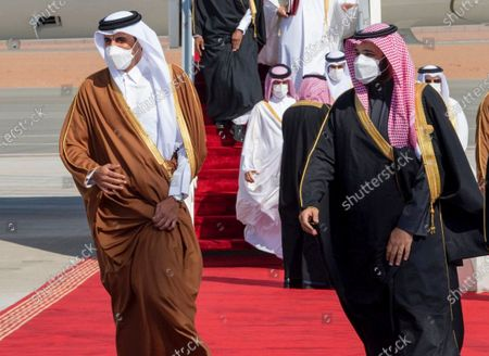 In this photo provided by the Saudi Royal Court, Saudi Arabia's Crown Prince Mohammed bin Salman, right, welcomes Qatar's Emir Sheikh Tamim bin Hamad al-Thani upon his arrival to attend the Gulf Cooperation Council's 41st Summit in Al-Ula, Saudi Arabia