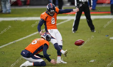 Stock Image of Denver Broncos kicker Brandon McManus (8) kicks as holder Sam Martin (6) places the ball in the first half of an NFL football game, in Denver