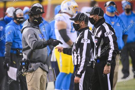 Los Angeles Chargers head coach Anthony Lynn talks to field judge Joe Blubaugh and line judge Tom Stephan (68) during the second half of an NFL football game against the Kansas City Chiefs, in Kansas City, Mo