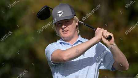 Stock Photo of Tanner Furyk, son of golfer Jim Furyk, watches his tee shot on the first hole during the first round of the PNC Championship golf tournament, in Orlando, Fla