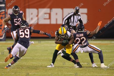 Green Bay Packers wide receiver Davante Adams (17) is tackled by Chicago Bears linebacker Josh Woods (55) and cornerback Kindle Vildor (22) during the second half of an NFL football game, in Chicago