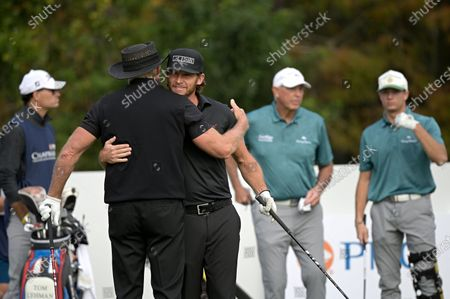 Greg Norman, left, of Australia, hugs his son Greg Norman Jr. before hitting their tee shots on the first hole during the final round of the PNC Championship golf tournament, in Orlando, Fla