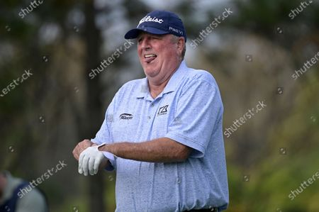 Mark Calcavecchia sets up for his tee shot on the fourth hole during the final round of the PNC Championship golf tournament, in Orlando, Fla
