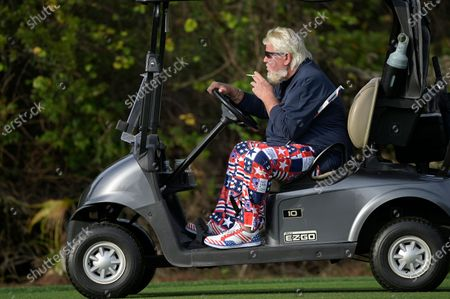 Stock Picture of John Daly drives a cart after hitting from the first fairway during the final round of the PNC Championship golf tournament, in Orlando, Fla