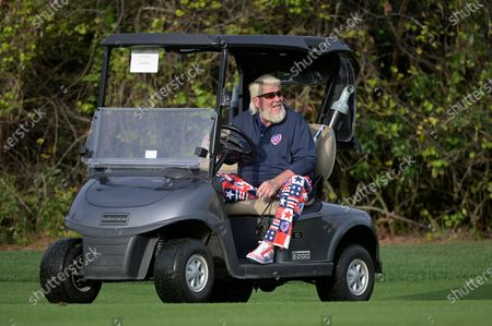 Stock Image of John Daly drives a cart after hitting from the first fairway during the final round of the PNC Championship golf tournament, in Orlando, Fla