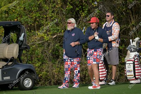 John Daly, left, watches his son Little John Daly, center, hit from the first fairway during the final round of the PNC Championship golf tournament, in Orlando, Fla
