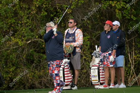 Little John Daly, second from right, watches his father John Daly, left, hit from the first fairway during the final round of the PNC Championship golf tournament, in Orlando, Fla