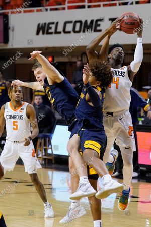 Oklahoma State guard Bryce Williams (14) grabs a rebound in front of West Virginia guard Sean McNeil (22) and guard Miles McBride (4) in the second half of an NCAA college basketball game, in Stillwater, Okla