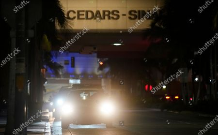Police vehicle idles outside Cedars-Sinai Medical Center, late, in Los Angeles. Music producer and hip hop legend Dr. Dre is hospitalized in the intensive care unit at Cedars-Sinai after suffering a brain aneurysm Monday