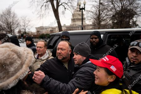 Flanked by personal security, Alex Jones leaves after speaking at a Stop the Steal rally in front of the Supreme Court on Tuesday, Jan. 5, 2021 in Washington, DC.