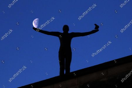 Stock Picture of An Antony Gormley statue on a building in the City centre looks like it's holding the half moon on one palm and has a pigeon on the other one on the first day of 'Lockdown Three' in Peterborough, Cambridgeshire. Prime Minister Boris Johnson last night announced there will be another national lockdown starting today, to help stop the spread of Coronavirus. Again, people are not allowed to leave home except for minimal food shopping, medical treatment, exercise - once a day, and essential work. COVID-19 Coronavirus third lockdown, Peterborough, Cambridgeshire, UK, on January 5, 2021