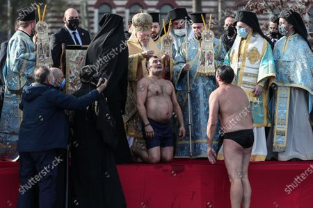 Stock Picture of Greek Orthodox Ecumenical Patriarch Bartholomew I (C) of Constantinople gives gold necklace to Greek Orthodox swimmer Vasili Kurukcu during the Epiphany Day ceremony in Istanbul, Turkey, 06 January 2021. Greek Orthodox swimmers take part in an annual race to retrieve a wooden crucifix thrown into the Bosphorus waters at the Golden Horn.