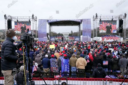 """With the White House in the background, Eric Trump speaks, in Washington, at a rally in support of President Donald Trump called the """"Save America Rally"""