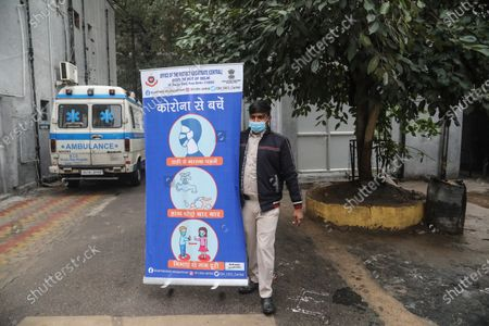 A health worker wearing protective mask carries the roller banner with Covid19 measure information during the dry run (mock drill) to test the mechanisms for covid-19 vaccine. Beneficiaries register themselves through Co-WIN official vaccine app for India. India requires a total of 6.6 crore doses of coronavirus vaccines to inoculate healthcare and frontline workers in which over 75 lakh health workers registered themselves. Indian Union Health Minister Dr. Harsh Vardhan announced that vaccination will be free for frontline workers.