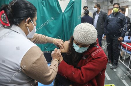 A health official wearing a protective mask holds a syringe with dummy vaccine to a volunteer while testing the mechanisms for covid-19 vaccine process during the dry run (mock drill).Beneficiaries register themselves through Co-WIN official vaccine app for India. India requires a total of 6.6 crore doses of coronavirus vaccines to inoculate healthcare and frontline workers in which over 75 lakh health workers registered themselves. Indian Union Health Minister Dr. Harsh Vardhan announced that vaccination will be free for frontline workers.
