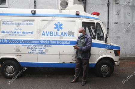 A health worker wearing protective mask stands next to his ambulance during the dry run (mock drill) to test the mechanisms for covid-19 vaccine. Beneficiaries register themselves through Co-WIN official vaccine app for India. India requires a total of 6.6 crore doses of coronavirus vaccines to inoculate healthcare and frontline workers in which over 75 lakh health workers registered themselves. Indian Union Health Minister Dr. Harsh Vardhan announced that vaccination will be free for frontline workers.