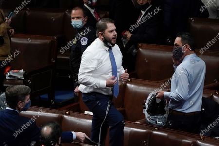 Rep. Ruben Gallego, D-Ariz., stands on a chair as lawmakers prepare to evacuate the floor as protesters try to break into the House Chamber at the U.S. Capitol, in Washington