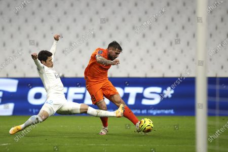Marseille's Hiroki Sakai, left, try to block the ball from Montpellier's Andy Delort celebrates after scores against Montpellier during the French League One soccer match between Marseille and Montpellier at the Stade Velodrome in Marseille, southern France