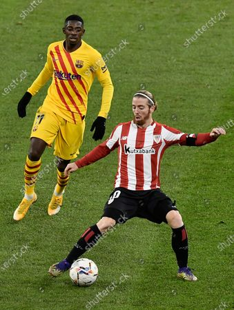 Athletic Bilbao's Iker Muniain, controls the ball in front of Barcelona's Ousmane Dembele during the Spanish La Liga soccer match between Athletic Bilbao and Barcelona at San Mames stadium in Bilbao, Spain