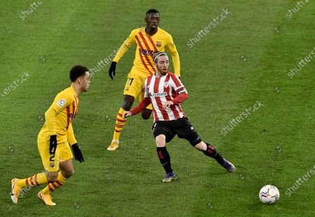 Athletic Bilbao's Iker Muniain, center, passes the ball in front of Barcelona's Sergino Dest, left and Ousmane Dembele, back, during the Spanish La Liga soccer match between Athletic Bilbao and Barcelona at San Mames stadium in Bilbao, Spain