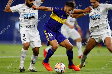 Eduardo Salvio of Argentina's Boca Juniors, center, scuffles with Felipe Jonatan of Brazil's Santos and Lucas Verissimo of Brazil's Santos during a Copa Libertadores semifinal first leg soccer match at the Bombonera stadium in Buenos Aires, Argentina