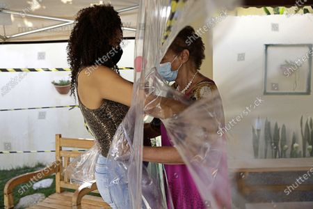Maria Amelia, right, hugs her niece Flaviana Silva through a plastic barrier during a visit to the Casa Clara home for the elderly in Brasilia, Brazil, . The home set up the system following the COVID-19 restrictions and protection measures for the elderly residents of the home