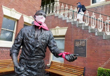The statue of former Australian cricket great Richie Benaud with a mask on as patrons arrive ahead of play on day one of the third cricket test between India and Australia at the Sydney Cricket Ground, Sydney, Australia