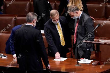 Stock Photo of Rep. Jim Jordan, R-Ohio, second from right, talks with Rep. Scott Perry, R-Pa., who objected to confirming the Electoral College votes from Pennsylvania during a joint session of the House and Senate to confirm the Electoral College votes cast in November's election, at the Capitol, early, in Washington