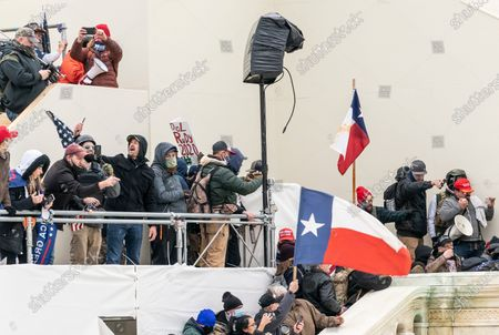 Stock Photo of Pro-Trump protester seen on balcony of Capitol building and holding poster with reference to Rudy Giuliani. Illegal invasion of Capitol building produced four death of protesters, 50 police officers were wounded and lots of property damaged.