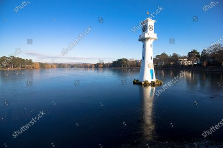The Captain Scott memorial clock tower is reflected in a partly frozen Roath Park lake in Cardiff as temperatures drop.