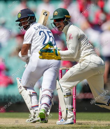 Australian captain and wicketkeeper Tim Paine, right, reacts as India's Cheteshwar Pujara hits the ball during play on day three of the third cricket test between India and Australia at the Sydney Cricket Ground, Sydney, Australia